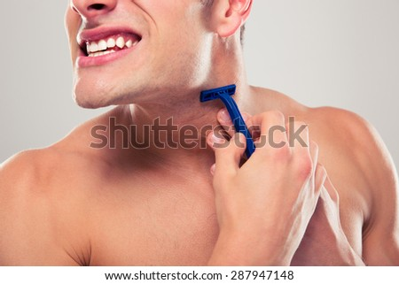 Man shaving over gray background - stock photo