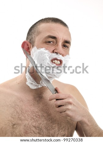 Man shaving with a knife. He has irritated skin and a lot of pain. - stock photo