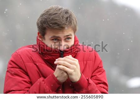Man shivering in cold winter and rubbing hands while is snowing - stock photo