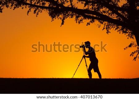 Man shooting a camera in a beautiful natural setting.  - stock photo