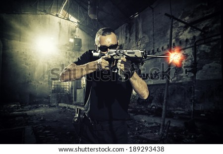 man shooting a gun and wearing sunglasses - stock photo