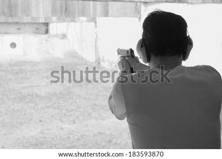 Man shooting at a target on an outdoor shooting range. - stock photo