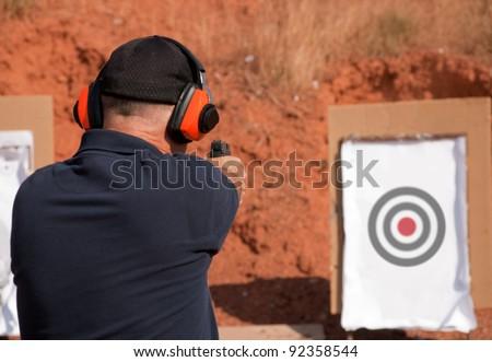 Man shooting at a target on an outdoor shooting range, focus on gun - stock photo