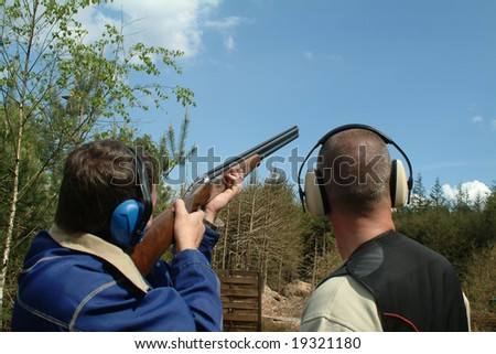 Man shooting clay pigeons being instructed - stock photo