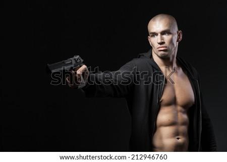 man shooting gun isolated on black background - stock photo