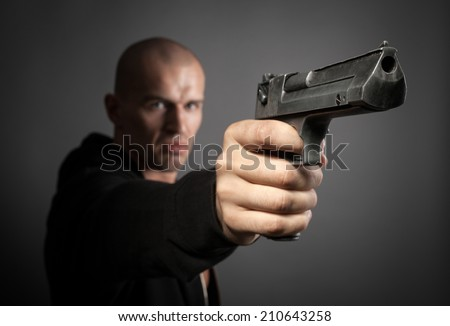 man shooting gun isolated on gray background. focus on gun