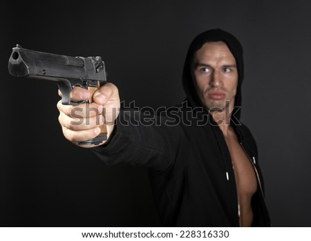 man shooting gun isolated on gray background. focus on gun - stock photo
