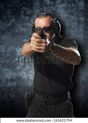 Man shooting hand gun - stock photo