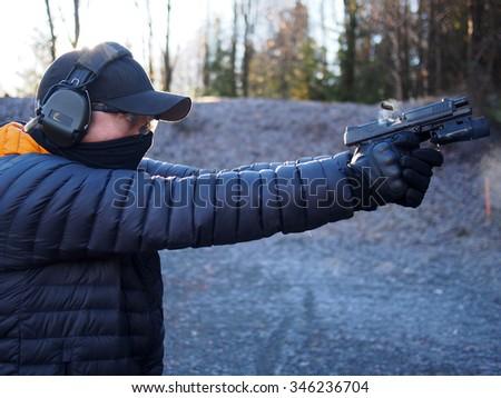 Man shooting handgun - stock photo