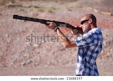 Man shooting shot gun. - stock photo