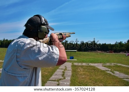 man shooting skeet with shotgun - stock photo