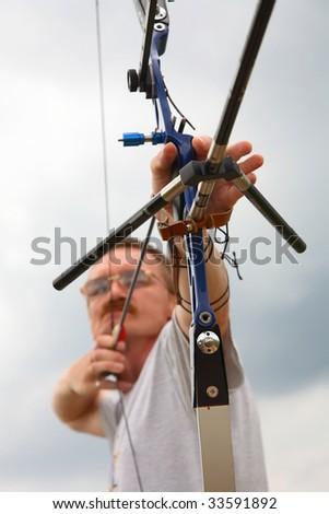 man  shooting to archery target. - stock photo