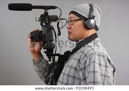 Man shooting video with a digital SLR camera with shotgun microphone and separate audio recorder.