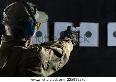 Man shooting with gun at a target in shooting range - stock photo