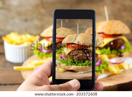 Man shooting with his cell phone camera big and tasty burgers.Selective focus on the phone - stock photo