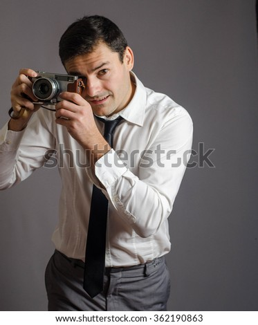 man shooting with old camera gray background and looking at camera