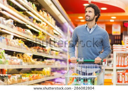 Man shopping in a supermarket - stock photo