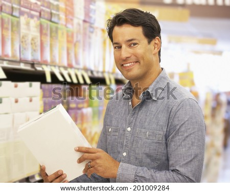 Man shopping in supermarket - stock photo