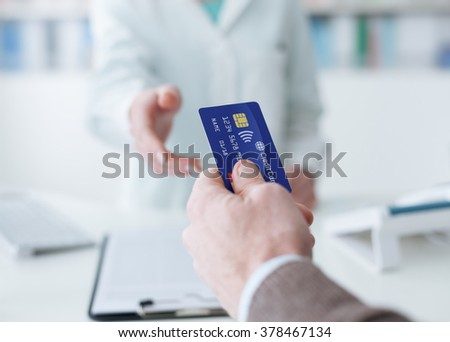 Man shopping in the pharmacy, he is giving the credit card to the cashier - stock photo