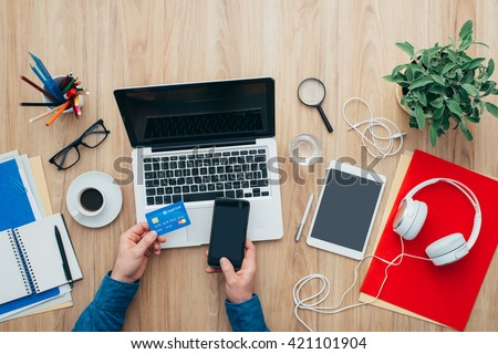 Man shopping online at home using a laptop and a credit card, he is making a mobile payment using his smartphone, top view - stock photo