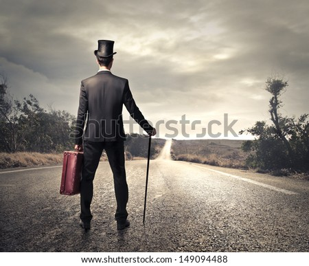 man shot from behind looking the desert road - stock photo