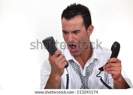 Man shouting at telephone - stock photo
