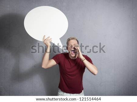 Man shouting loudly while holding white blank speech bubble with space for text isolated on grey background. - stock photo
