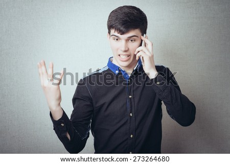 Man shouting on the phone. Gesture cry discontent, talking on the phone. On a gray background - stock photo