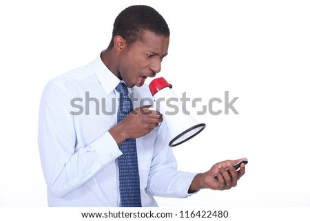 Man shouting through a megaphone at a cellphone - stock photo