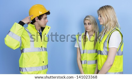 Man Shouting To Female Worker For Not Wearing Hard Hat Over Blue Background