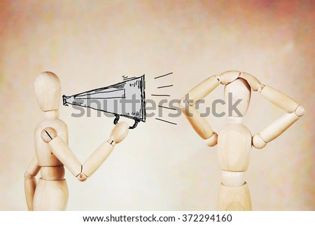 Man shouts to another one with a megaphone. Abstract image with a wooden puppet - stock photo
