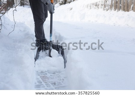 man shoveling snow away from walkway - stock photo
