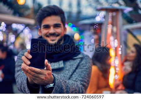 Man Shoving His Smartphone To The Camera On Winter Market