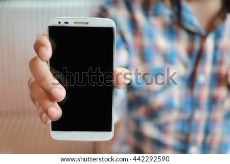 man show his smart phone, man hand using mobile phone ,young adult using mobile smart phone, Internet of things lifestyle with wireless communication and internet with smart phone.  - stock photo