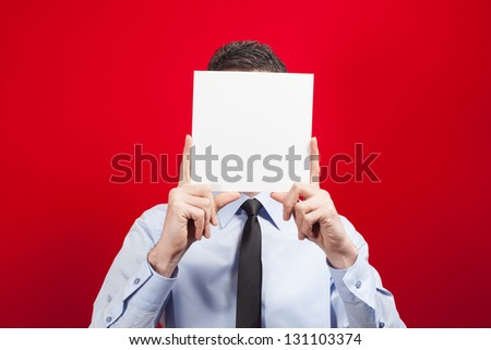 Man showing a blank paper sheet in front of his head - stock photo