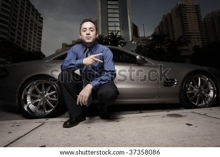 Man showing a peace sign by a luxury sports car