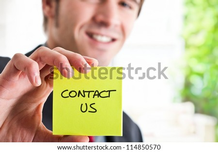 Man showing a post-it with contact - stock photo