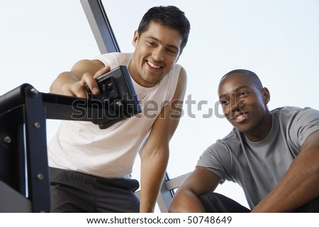 Man showing another man how to use control panel of exercise machine