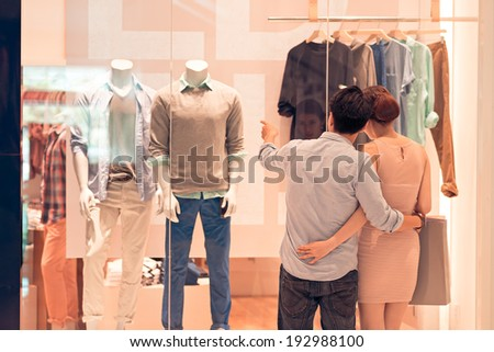 Man showing clothes in the shop window to his girlfriend, rear view - stock photo