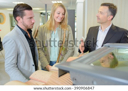 Man showing couple display of roof tiles