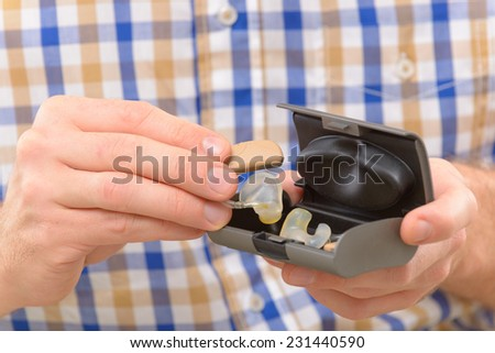Man showing deaf aid in ear - stock photo