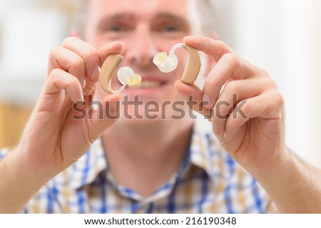 Man showing deaf aids in hands - stock photo