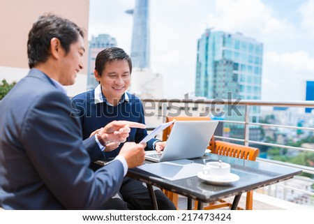 Man showing document to his colleague while they are drinking coffee in the rooftop cafe - stock photo