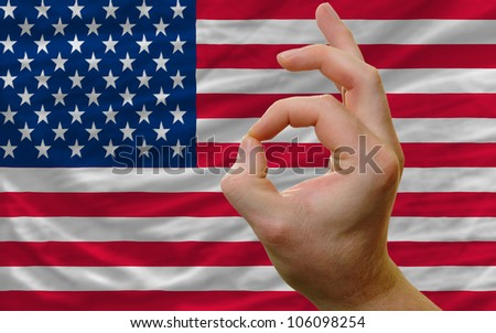 man showing excellence or ok gesture in front of complete wavy america national flag of  symbolizing best quality, positivity and success