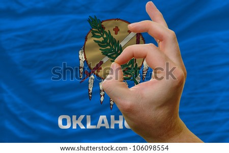 man showing excellence or ok gesture in front of complete wavy american state flag of oklahoma symbolizing best quality, positivity and success - stock photo