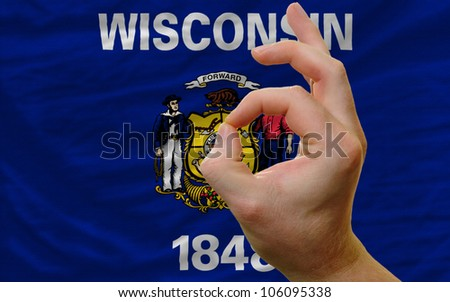 man showing excellence or ok gesture in front of complete wavy american state flag of wisconsin symbolizing best quality, positivity and success - stock photo