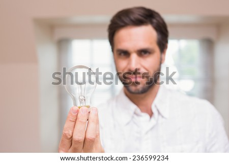 Man showing light bulb to camera at home in the living room - stock photo