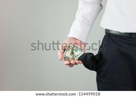 Man showing little bit of money left in his pocket - stock photo