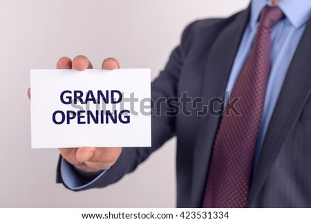 Man showing paper with GRAND OPENING text