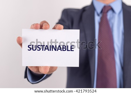 Man showing paper with SUSTAINABLE text - stock photo